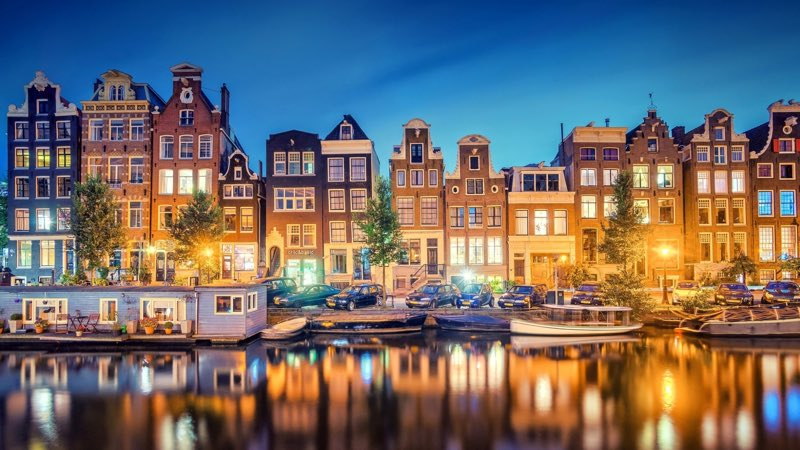 Buildings Canal Boats night lights in Amsterdam travel guide